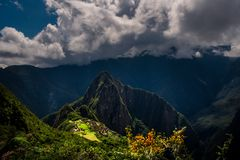 Majestic aerial view on the Machu Picchu / Huayna Picchu mountain. With Incan sacred city ruins during the sunset. Beautiful greenery in the foreground stock photography