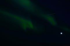 Majestic aurora borealis dancing around full moon Stock Photo