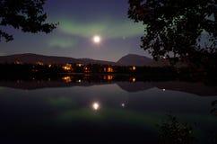 Majestic aurora borealis, northern light over calm mirror lake at night Stock Images