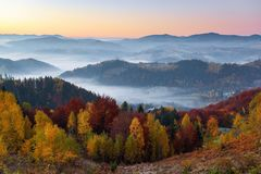 Majestic autumn rural scenery. Landscape with beautiful mountains, fields and forests covered with morning fog. stock photo