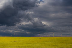 Majestic and beautiful rural landscape with yellow field and a thunderstorm with dark clouds Stock Image