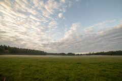 Majestic country landscape under morning sky with clouds. Stock Photo