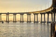 The majestic curve of the Coronado Bridge as the early morning bathes the stark concrete. Coronado bridge over sun filled bay; San Diego California; the coast of royalty free stock photos
