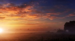 Majestic dramatic scene. fantastic foggy sunset over the meadow with colorful clouds on the sky. picturesque rural landscape, mist stock images