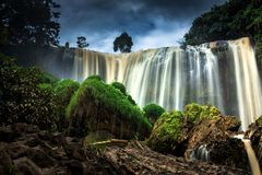 Nature Landscape with Blurred Falls, Rough Rocks, Green Grass and Dark Clouds stock image