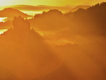 Majestic golden sunrise in a beautiful mountain. Sandstone rock increased from gold foggy valley background. Royalty Free Stock Photos