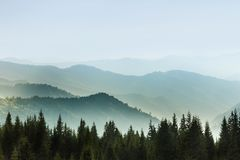 Majestic landscape of summer mountains. A view of the misty slopes of the mountains in the distance. royalty free stock images
