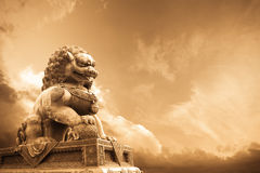 Majestic lion statue. A majestic lion statue in the forbidden city with changing sky stock image