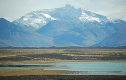 Majestic Mountain. Snow-covered majestic mountain before fields and lake in Patagonia Royalty Free Stock Images