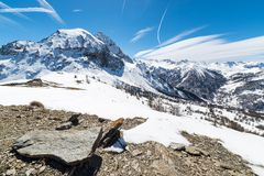 Majestic mountain peaks in the Alps. Majestic wide angle view of snowcapped high mountain peaks in the italian alpine arc, in a bright sunny day of spring, near Royalty Free Stock Photos