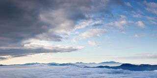 Majestic natural view of the mountains in the clouds. Majestic view of nature. Morning fog under the mountaintops. Panorama with amazing clouds over a mountain royalty free stock photo