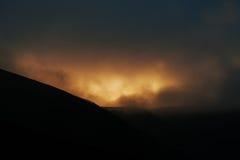 Majestic orange light of sun on dusk shadow of mountains on fog. Royalty Free Stock Photography