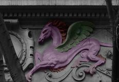 The majestic pink pegasus. Shot in black and white and painted in colors, details on the sculpture on the facade of this historic building representing some Stock Photo