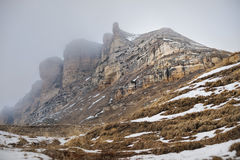 Majestic rocks of the Caucasus in foggy clouds with snow at the foot Stock Photos