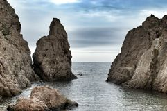 Majestic rocks in the Mediterranean Sea. This photo was taken in Tossa de Mar (Catalonia, Spain). Majestic rocks, dark clouds and infinite sea...Impressive view Stock Images