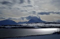 Majestic snowy winter landscape with blue sea and mighty mountain peaks Stock Photography