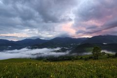 Majestic spring day. A beautiful landscape with high mountains, sky with clouds and sunset. Dense fog with beautiful light. stock photo