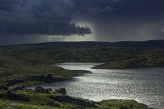 Majestic stormy sky and sun beams over a lake in the mountains. Stock Photo