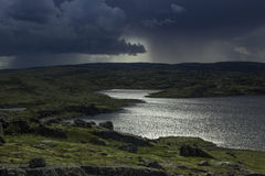 Majestic stormy sky and sun beams over a lake in the mountains. Stock Images