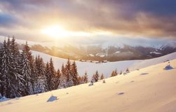 Majestic sunset at small village on a snowy hill under Ukrainian. Villages in the mountains in winter. Beautiful winter. Landscape. Carpathians, Ukraine, Europe Stock Photography