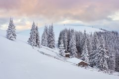 Majestic sunset at small village on a snowy hill under Ukrainian. Villages in the mountains in winter. Beautiful winter. Landscape. Carpathians, Ukraine, Europe Royalty Free Stock Images