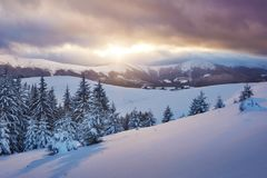 Majestic sunset at small village on a snowy hill under Ukrainian. Villages in the mountains in winter. Beautiful winter. Landscape. Carpathians, Ukraine, Europe Stock Image