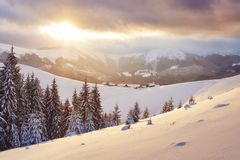 Majestic sunset at small village on a snowy hill under Ukrainian. Villages in the mountains in winter. Beautiful winter. Landscape. Carpathians, Ukraine, Europe Stock Images