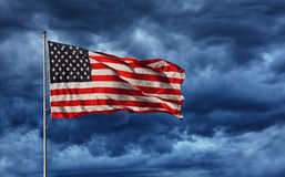Majestic United States Flag. A bold and majestic U.S. Flag flying with dark storm clouds looming. It shines despite its dark surroundings Royalty Free Stock Image