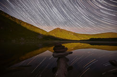 Majestic view of alpine lake with starry sky. Magic night landscape with mountains, lake and amazing starry sky, star trails in the night sky, pyramid of stones Royalty Free Stock Photo