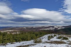 Majestic view of cloudy sky, winter mountain, snowy glade, residential district, conifer and deciduous forest from Plana mountain. Toward Balkan mountain or royalty free stock images
