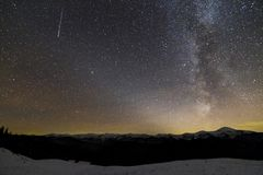 Majestic view of fantastic starry dark sky on winter night. Milky Way and falling star over magnificent mountain ridge snow-capped. Peaks. Breathtaking panorama royalty free stock images