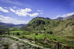 Majestic view on scenic, green mountain valley with lake and blue sky above horizon. Pristine environment of Snowdonia National Park ,North Wales,UK in royalty free stock photos