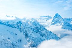 Majestic view of winter sunny day of Dombaj mountains with blue. Sky and clouds stock photography