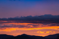 Majestic vivid sunset/sunrise with clouds over dark mountains Royalty Free Stock Images