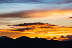 Majestic vivid sunset/sunrise with clouds over dark mountains Royalty Free Stock Image