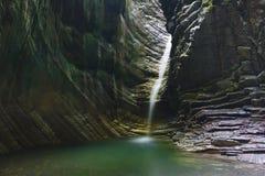 Majestueuze diepe grot met het gieten van verfrissende waterval stock foto