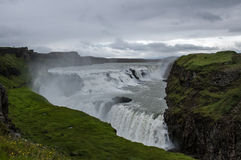 Majestueuze watervallen met rond rotsen en gras Stock Fotografie