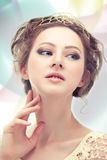 Majesty. Young majestic woman in a diadem of gold on abstract background Stock Photos