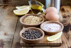 Majonezowi składniki na drewnianych tło soli pieprzu jajek cytryny oleju Nieociosanych składnikach dla kumberland kopii przestrze Obrazy Royalty Free