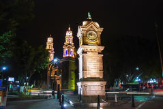 Major central park and square in Puebla de Zaragoza, Mexico. With illuminated clock tower and Cathedral Royalty Free Stock Photos