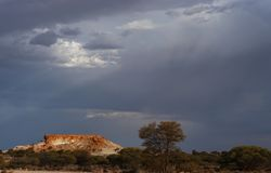 Major Thunderstorm approaching breakaways. Dark ominous clouds forming for a thunderstorm in the outback of Australia. Sunlit breakaways underneath a terrible stock photography