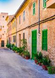 Majorca, beautiful street with mediterranean houses at the old town of Alcudia, Spain. Street with flowers and plant pots in the historic city center of Alcudia royalty free stock photo