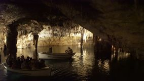Tourists float on a boat on the underground lake in the famous stalactite caves of Drach stock video