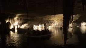 Tourists float on a boat on the underground lake in the famous stalactite caves of Drach stock video footage