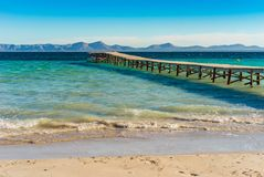 Majorca, wooden pier at the beach of bay of Alcudia, Spain Balearic Islands. Beach at the bay of Alcudia on Mallorca island, Spain Stock Image