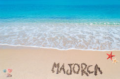 Majorca writing. Turquoise water and golden sand with shells and sea stars and majorca written on it Stock Images