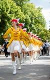 Majorettes en los trajes blancos, amarillos y rojos Fotos de archivo