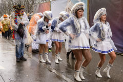Majorettes marching wrapped up against rain at Carnival parade, Royalty Free Stock Photography
