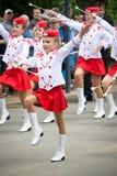 Majorettes menores desconocidos en los trajes blancos y rojos con los bastones Fotos de archivo