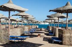 Straw umbrellas on  beach of the Red Sea, Hurghada, Egypt. Makadi beach. Hurghada – January 2016 Royalty Free Stock Photo